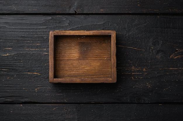 Boîte ou conteneur en bois rustique avec espace de copie pour le texte ou la nourriture, vue de dessus à plat, sur fond de table en bois noir