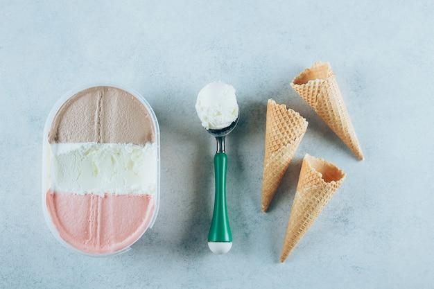 Boîte de crème glacée, une cuillère avec une boule et trois cônes de gaufres. glace au chocolat, fraise, sundae