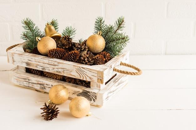 Boîte décorative en bois faite de leurs propres mains avec des boules d'or et des cônes d'épinette du nouvel an sur une table en bois.