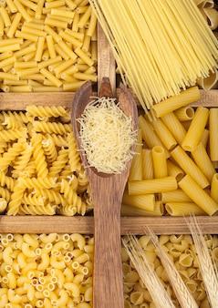 Boîte avec diverses pâtes classiques et cuillère en bois à spaghetti. vue de dessus