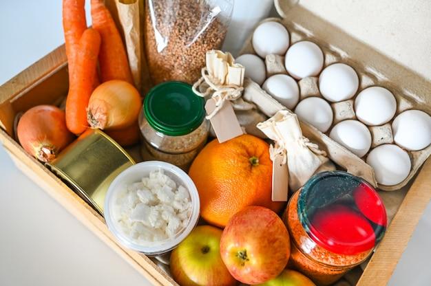 Boîte de donation bénévole avec divers produits pour les pauvres. pénuries alimentaires de coronavirus pandémique. dons de nourriture ou mur de concept de livraison blanc isolé.