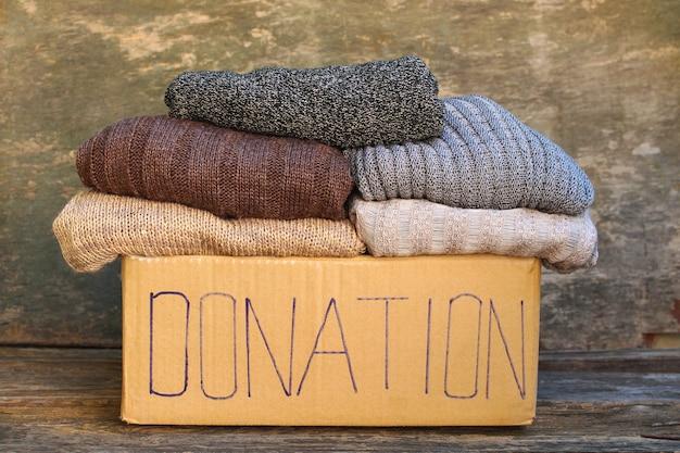 Boîte de dons avec des choses chaudes sur du vieux bois.
