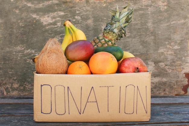 Boîte de dons avec de la nourriture sur fond de bois ancien.