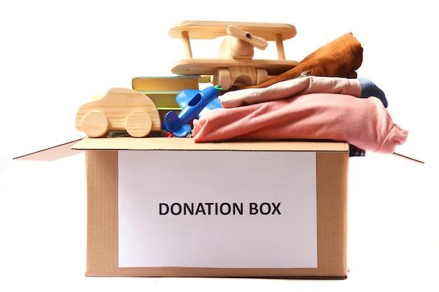 Boîte de dons avec des vêtements et des jouets isolés sur blanc