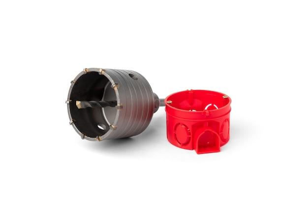 Boîte électrique d'installation rouge pour prises et couronne de diamant isolé sur fond blanc.