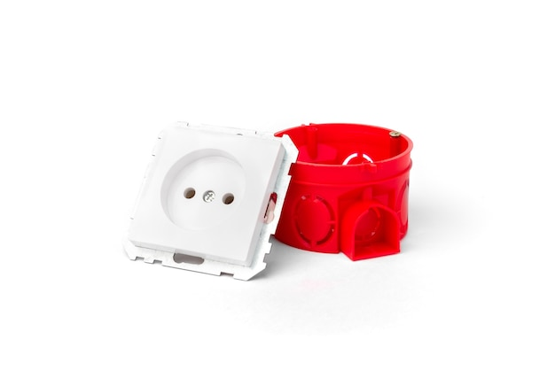 Boîte électrique d'installation rouge pour prises et prise blanche et fils sur fond de béton.