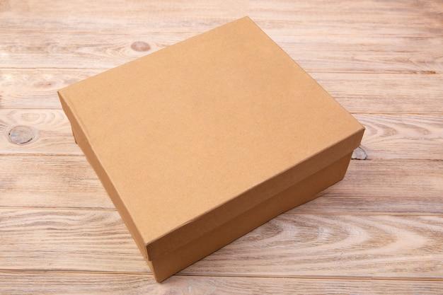 Boîte d'emballage en carton artisanale présentée sur une table en bois.