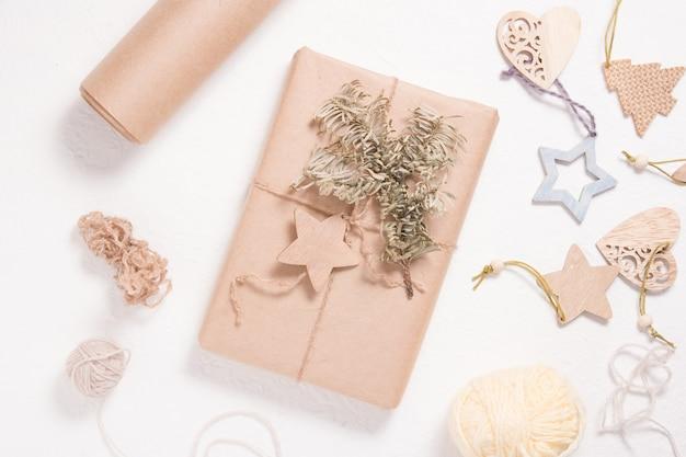 Boîte d'emballage écologique pour noël ou nouvel an, décorations de noël en bois, boîte enveloppée dans du papier kraft avec une branche d'épicéa et un coeur en bois sur fond blanc