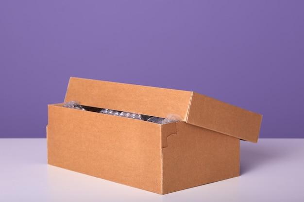 Boîte entrouverte pour noël ou autres vacances à la main présente en papier kraft marron sur le bureau.