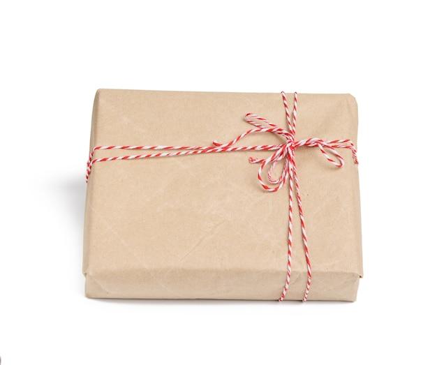 Boîte enveloppée dans du papier kraft brun et attachée avec une corde rouge, cadeau isolé sur fond blanc