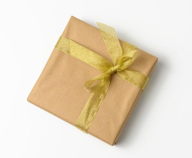 Boîte enveloppée dans du papier kraft brun et attachée avec ruban golen, cadeau sur fond blanc