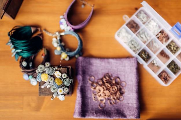 Boîte avec équipement pour travaux d'aiguille, bracelets sur table en bois, vue de dessus. bijoux faits à la main. artisanat, fabrication de bijouterie
