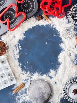 Boîte à farine concept de cuisson en bleu foncé avec accessoires, outils et aliments sucrés gâteau, gâteau, tarte, ingrédients: sucre, œufs, cacao, cannelle. vue de dessus plat pose la pâte concept