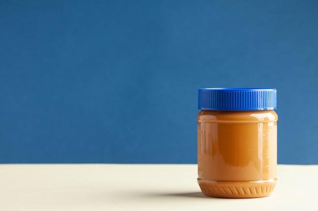 Boîte fermée de beurre d'arachide sur un dessert de petit déjeuner de culture américaine de fond coloré pour vegetaria...