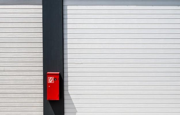 Boîte à feu rouge accrochée à une surface en noir et blanc avec des lignes