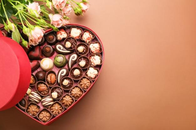Boîte en forme de coeur avec des bonbons au chocolat et des fleurs sur la couleur