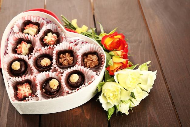 Boîte en forme de coeur avec des bonbons et des fleurs sur un fond en bois, gros plan