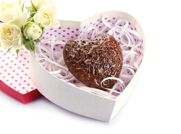Boîte en forme de coeur et bonbons avec des fleurs, gros plan