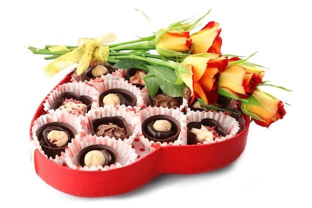 Boîte en forme de coeur avec des bonbons et des fleurs, isolé sur blanc