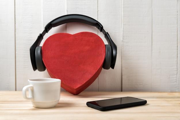 Boîte en forme de coeur avec un casque, un téléphone et une tasse. concept de musique d'amour.