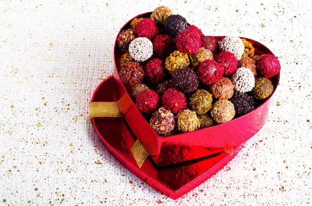 Boîte en forme de coeur avec des chocolats. bonbons à la main.