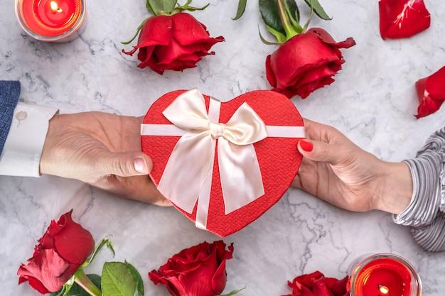Boîte en forme de coeur femelle et rouge avec un nœud en satin entouré de roses et de bougies