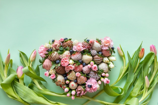 Boîte en forme de coeur avec des fraises recouvertes de chocolat à la main avec différentes garnitures et fleurs en cadeau le jour de la saint-valentin sur fond rose avec un espace libre pour le texte