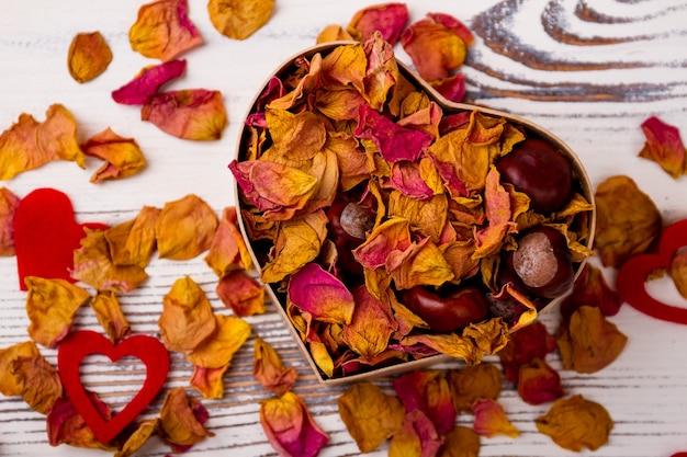 Boîte en forme de coeur avec des pétales séchés de châtaignes de pot-pourri rose et un design de coeurs le jour de l'amour