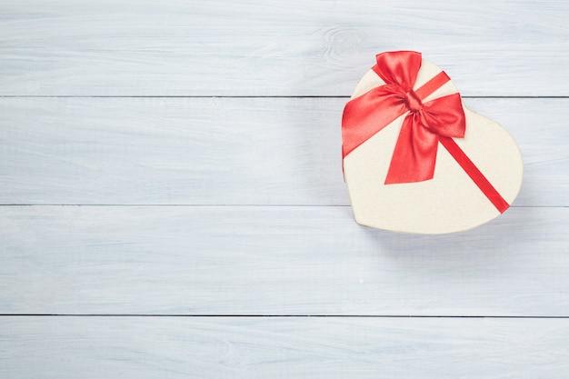 Boîte en forme de coeur avec ruban sur bois blanc avec espace libre pour votre texte.