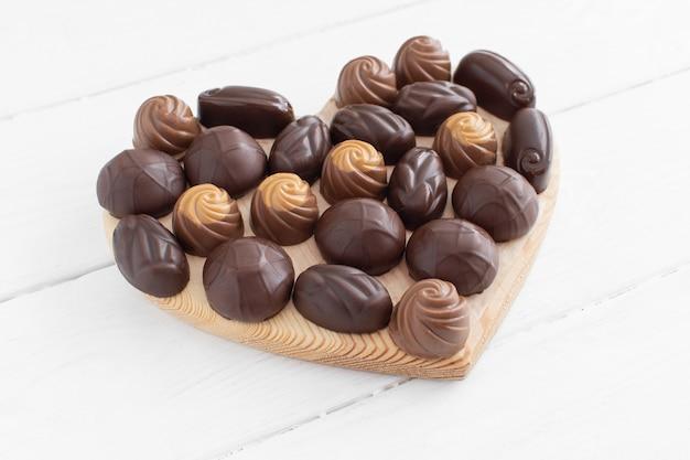 Boîte en forme de coeur de la saint-valentin avec des chocolats sur un blanc