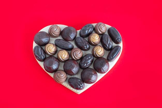 Boîte en forme de coeur de la saint-valentin avec des chocolats sur fond rouge