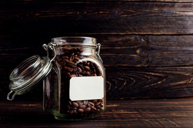 Une boîte de grains de café se dresse sur une table en bois.