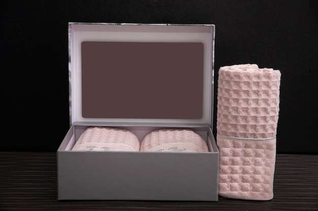 Boîte grise avec des serviettes roses sur fond sombre.