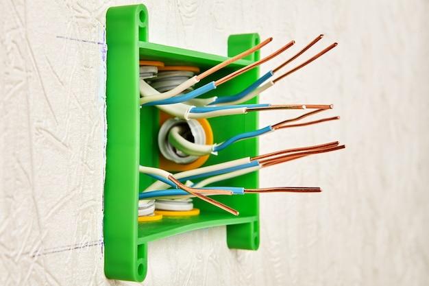 Boîte de jonction rectangulaire en plastique au stade de l'installation, les extrémités des fils de cuivre nus sont préparées pour la connexion.