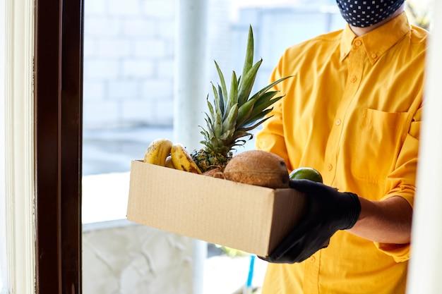 Boîte de livraison de courrier homme avec des fruits exotiques, livraison sans contact.