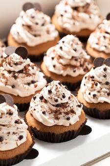 Boîte de livraison avec des petits gâteaux au café décorés de crème au beurre de moka et de pépites de chocolat