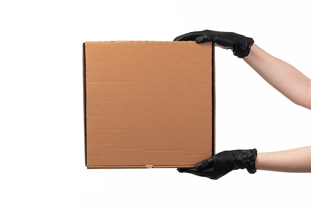 Une boîte de livraison vue de face tenir par la main féminine dans des gants noirs sur un bureau blanc
