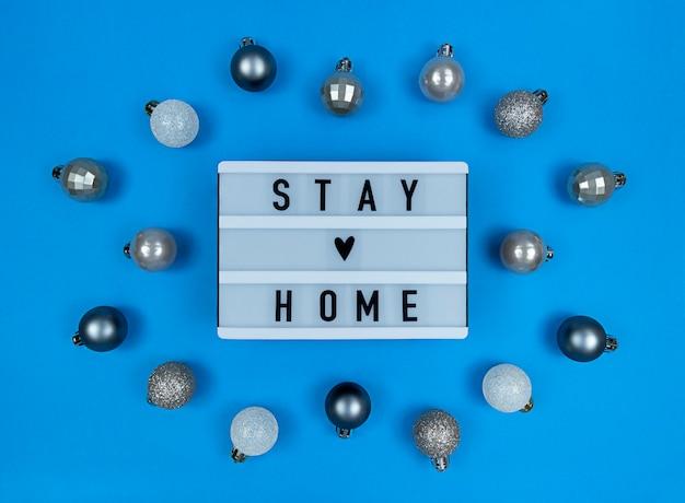 Boîte à lumière avec devis de séjour à la maison avec des boules de noël.