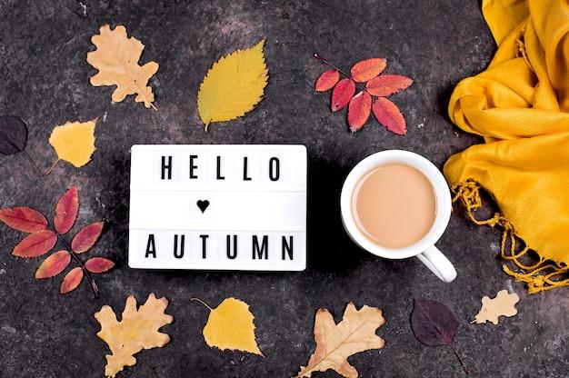 Boîte à lumière avec des mots bonjour l'automne, tasse de café et feuilles d'automne colorées