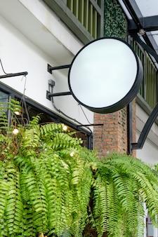 Boîte à lumière de signe de magasin rond vide accroché sur un café rétro avec des feuilles de plantes