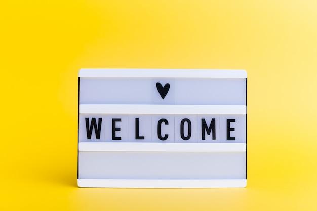 Boîte à lumière avec texte, bienvenue, sur mur jaune