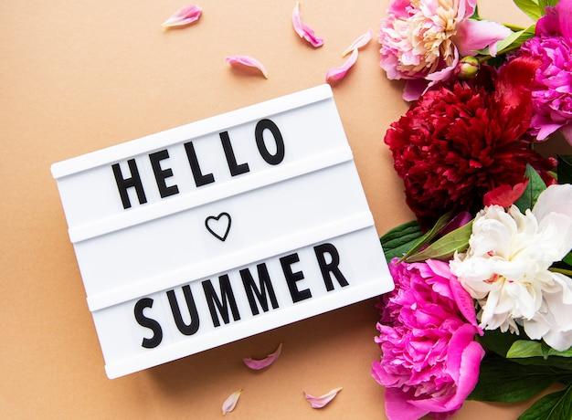 Boîte à lumière avec texte hello summer et fleurs de pivoines sur une surface brune