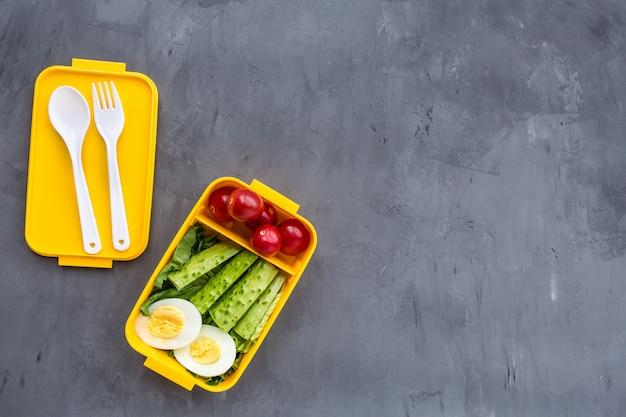 Boîte à lunch avec des aliments sains sur fond gris