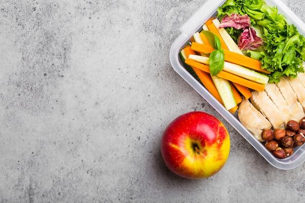 Boîte à lunch d'aliments sains pour le bureau ou l'école : filet de poulet, carotte, bâtonnets de concombre, salade, pomme. préparation et emballage de repas pour soutenir un mode de vie ou un régime équilibré, fond de pierre, espace de copie