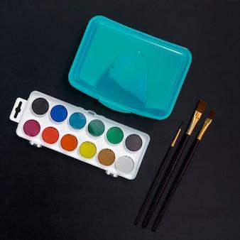 Boîte à lunch, aquarelles et pinceaux sur tableau noir