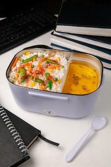 Boîte à lunch chauffée pour transporter et conserver les aliments. sur la table du bureau. a proximité se trouve une cuillère. dans la boîte, il y a du riz avec des légumes et de la soupe.