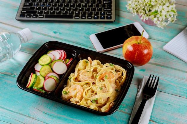 Boîte à lunch contenant des pâtes et des crevettes, du concombre et des radis sur une table en bois avec ordinateur portable.
