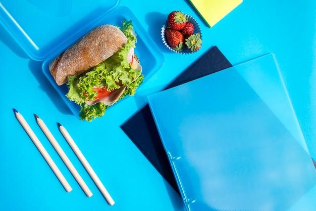 Boîte à lunch avec des dossiers et des crayons