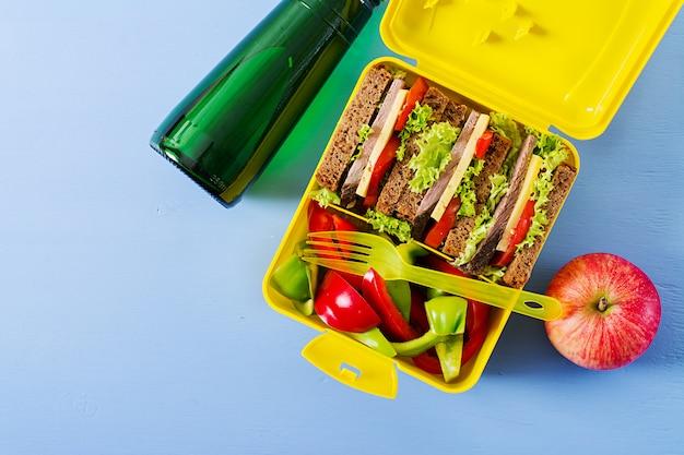 Boîte à lunch école saine avec sandwich au boeuf et légumes frais, bouteille d'eau et fruits sur table bleue. vue de dessus. mise à plat