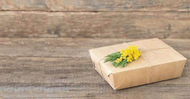 Boîte à lunch écologique avec brin de mimosa sur surface en bois